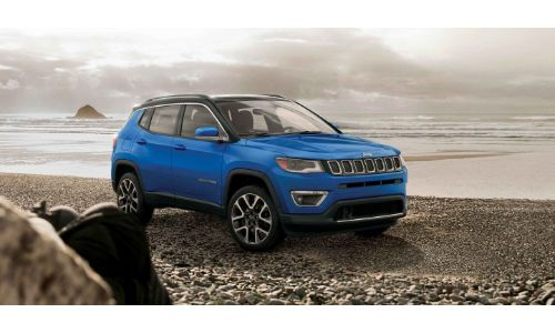 2019 Jeep Compass exterior shot with laser blue pearl paint color parked on a beach of gravel and rocks underneath the water and a foggy sky of clouds