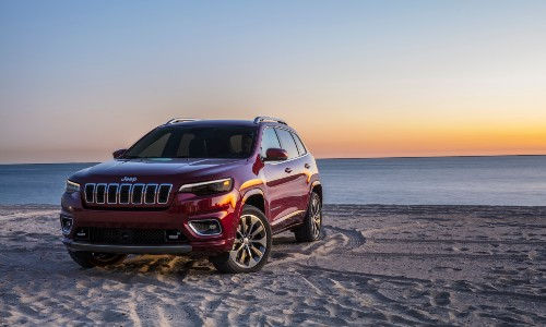 2020 Jeep Cherokee exterior shot with red paint color parked on a sand beach as the sun sets over the sea