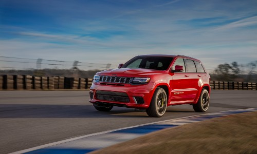 2020 Jeep Grand Cherokee Trackhawk exterior shot with red paint color driving around a racetrack