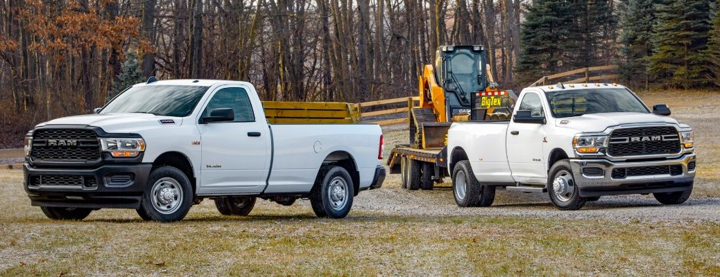 2020 Ram 2500 and 2020 Ram 3500 Tradesman Heavy Duty truck models with white paint color parked on a cold grass field near a barren fall forest