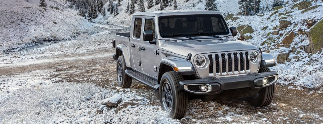 2020 Jeep Gladiator North Edition exterior shot with silver paint color parked on a rode in a snowy mountain wilderness