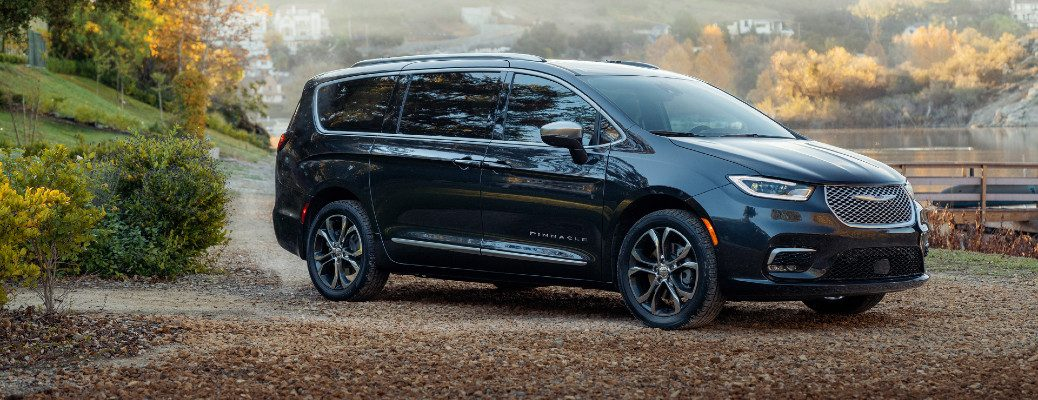 2021 Chrysler Pacifica Pinnacle exterior side shot parked on fallen leaves outside a farm and lake