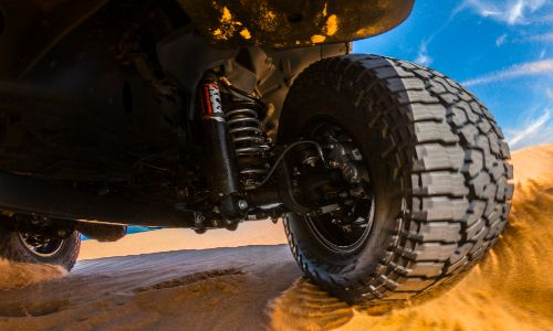 2020 Jeep Gladiator Mojave exterior shot closeup of tire treads and shocks while driving over sand