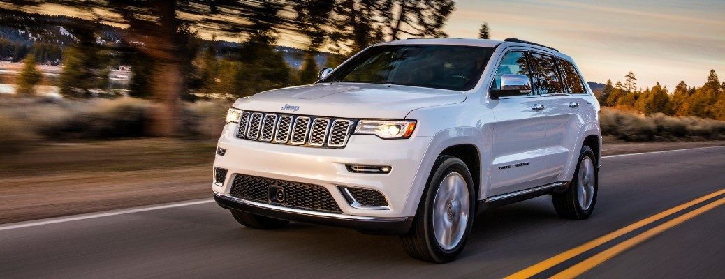 2020 Jeep Grand Cherokee Summit exterior shot with bright white paint color driving on a higher near fall trees