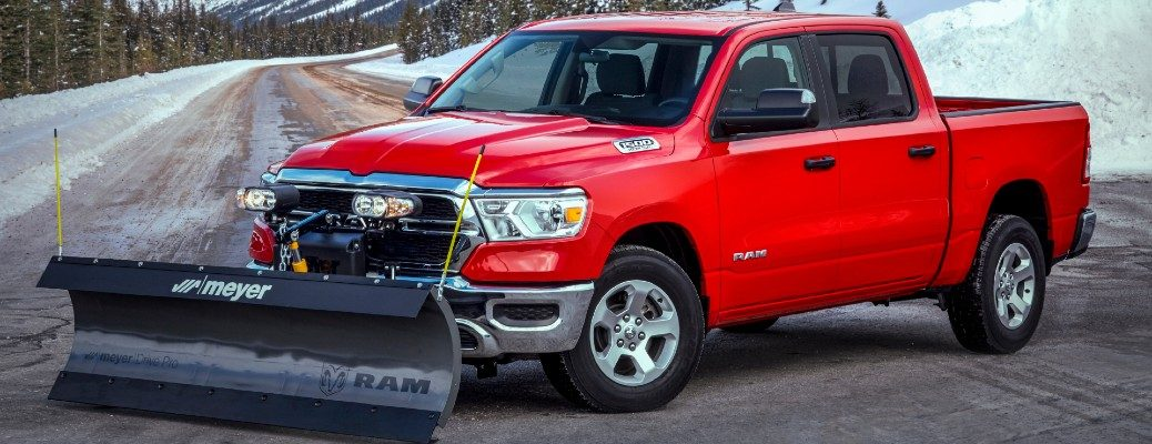2021 Ram 1500 Snow Plow Prep Package exterior shot with red paint color parked on a country road by a huge snow pile hill