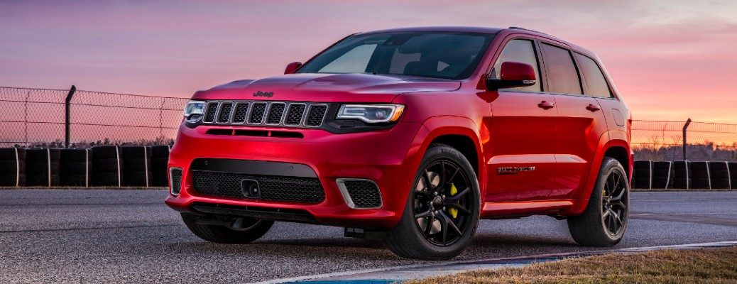 2020 Jeep Grand Cherokee Trackhawk exterior shot with red paint color parked on a racetrack at sunset