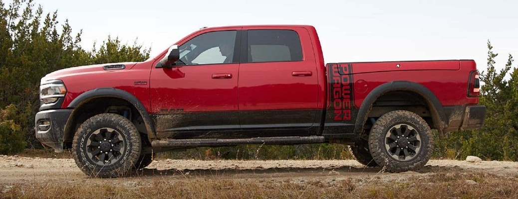 2020 Ram 2500 Power Wagon exterior side shot in red parked on a plain of dry grass near a forest of trees