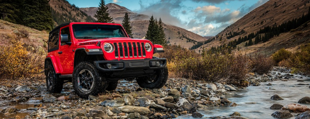 2020 Jeep Wrangler Rubicon exterior shot with red paint color parked by grass mountains and a stone creek
