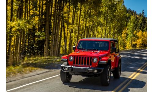 2020 Jeep Wrangler Rubicon exterior shot with firecracker red paint color driving alongside a forest under the sun
