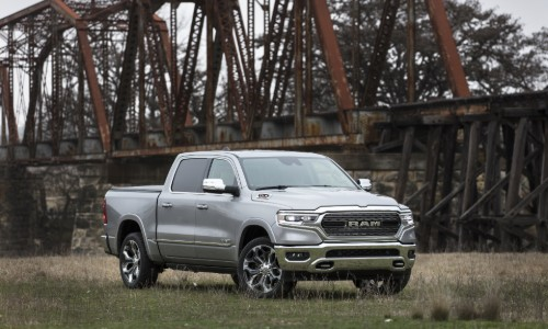 2020 Ram 1500 EcoDiesel exterior shot with gray metallic paint color parked in a grass clearing near an old and rusty bridge small