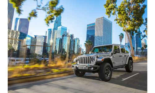2021 Jeep Wrangler 4xe exterior shot parked on a road with shiny skyscrapers in the background