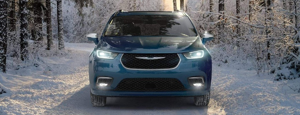 2021 Chrysler Pacifica Pinnacle exterior front shot in Fathom Blue parked in the middle of a snowy forest