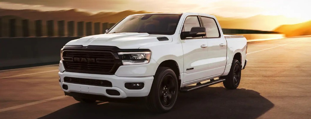 The front and side view of a white 2021 RAM 1500 parked during sunset.