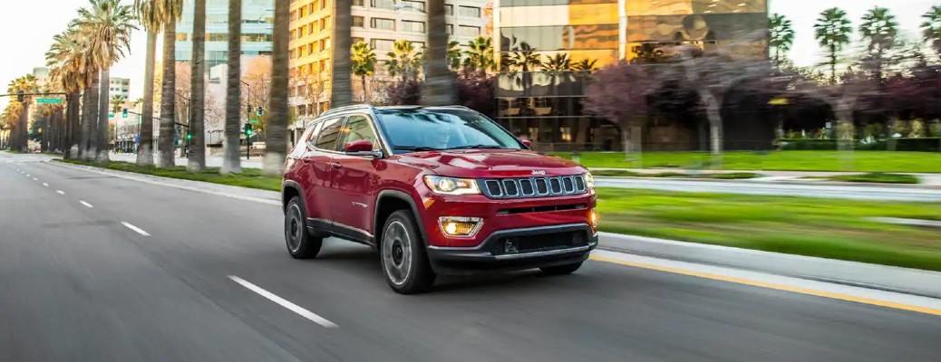 The front and side view of a dark red 2021 Jeep Compass driving down a road.