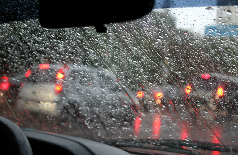 Raindrops cover a windshield.