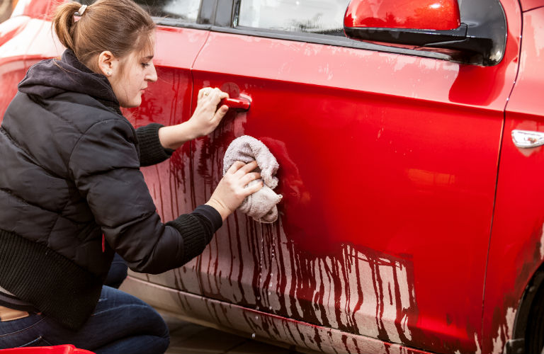 Woman Cleans grime off of her car.
