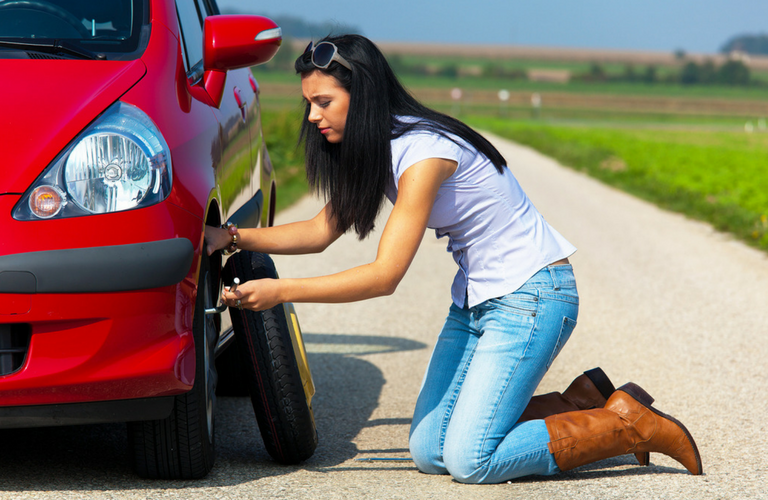Woman changes flat tire