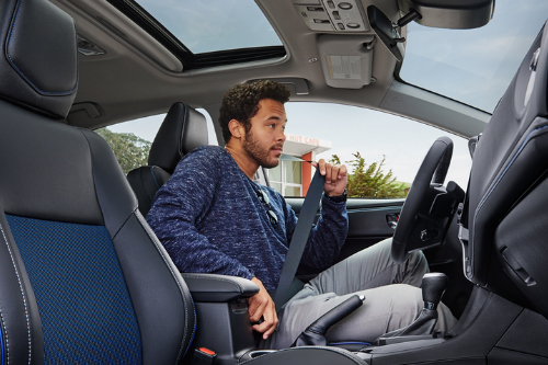 Driver buckling up in the front seat of the 2018 Toyota Corolla