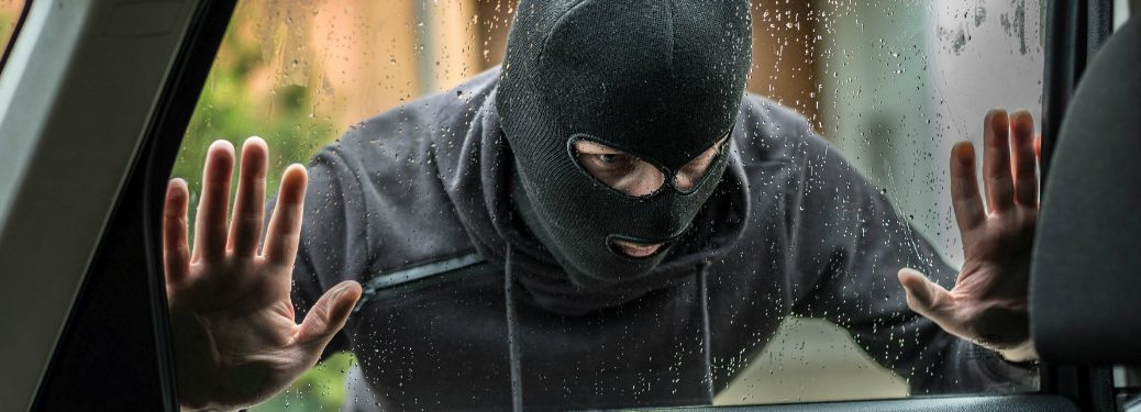 Man in a black mask looking into a car window