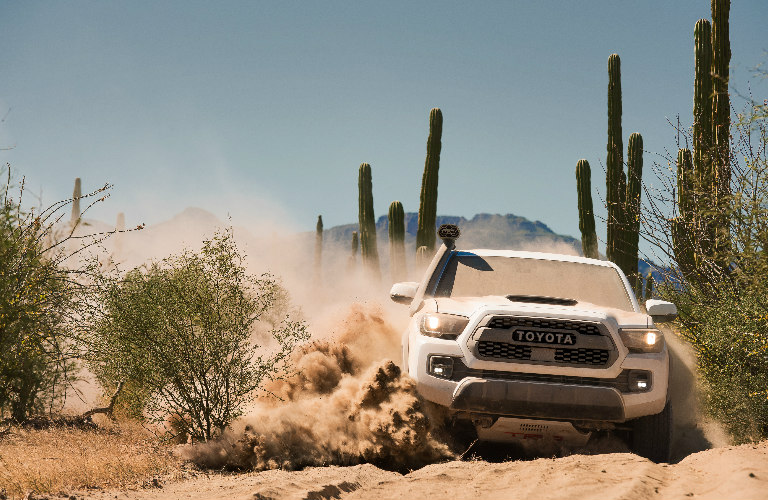 2019 Toyota Tacoma TRD Pro kicking up dirt as it drives through the desert