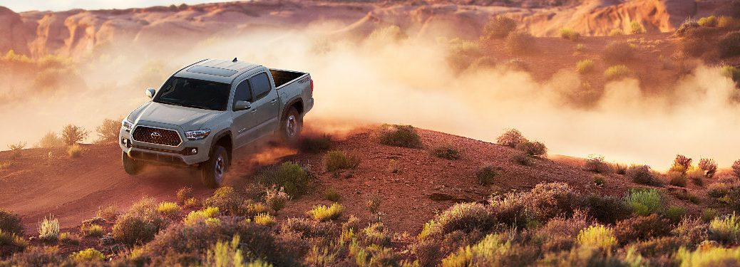 2018 Toyota Tacoma in gray driving on a dirt road in the desert
