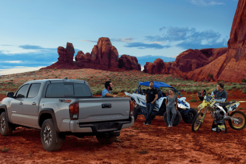 Friends gathered around a 2018 Toyota Tacoma with a dirt bike and dune buggy