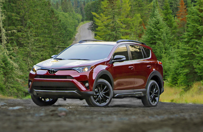 2018 Toyota RAV4 in red parked on a road in the woods