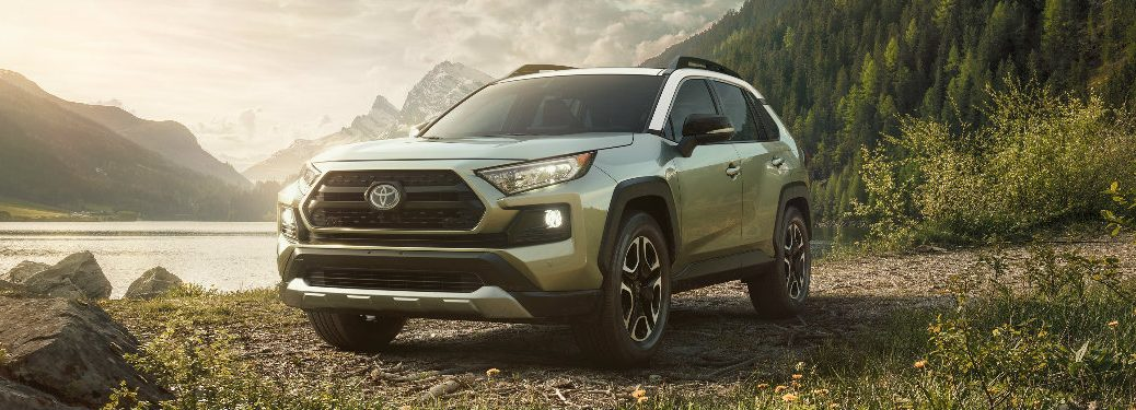 2019 Toyota RAV4 parked on a gravel lot in front of a lake surrounded by mountains