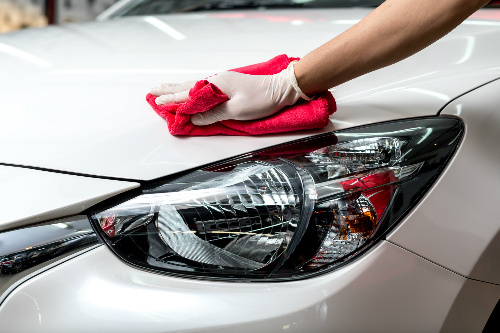 Someone cleaning a car exterior and headlights with a red cloth