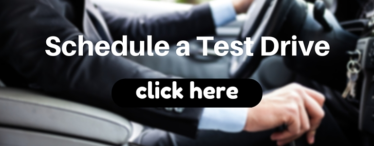 man in suit driving a car with the words schedule a test drive click here overlaid on top