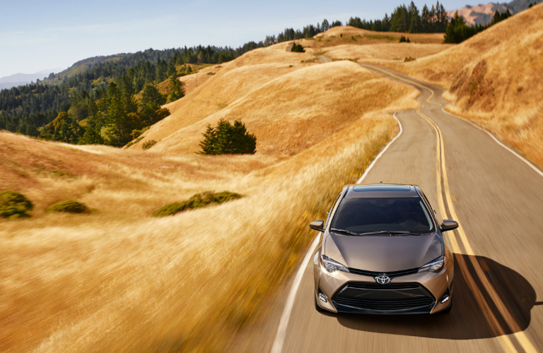 2019 Toyota Corolla in blue driving down a long stretch of country road