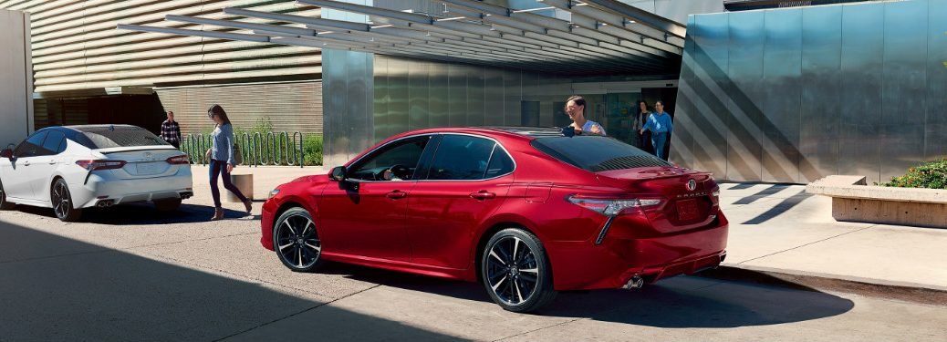 2019 Toyota Camry in red parked in front of a modern building