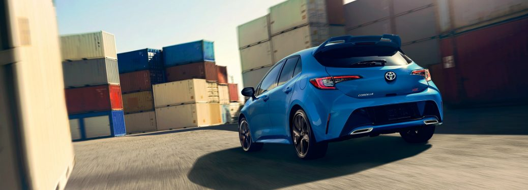 2019 Toyota Corolla Hatchback in Blue Flame driving in a maze of shipping containers