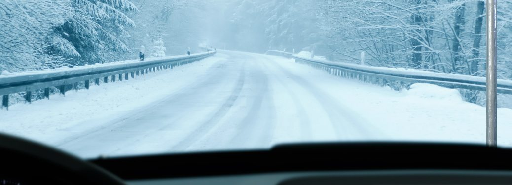 View out of the windshield of an empty snowy road