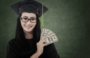Woman in a black cap and gown holding up a handful of money
