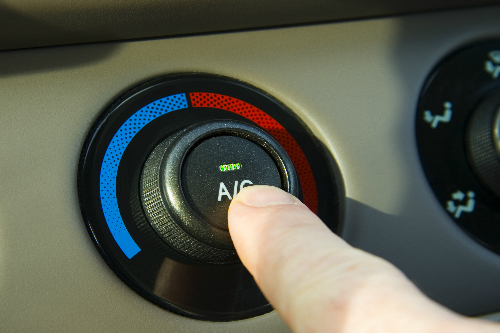 Someone pushing the AC button inside a car