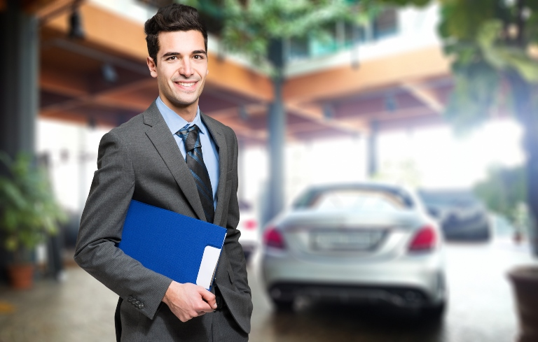 salesman smiling with car in background