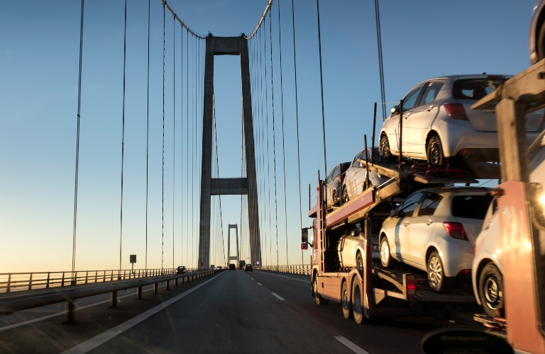 Truck with new cars going over bridge