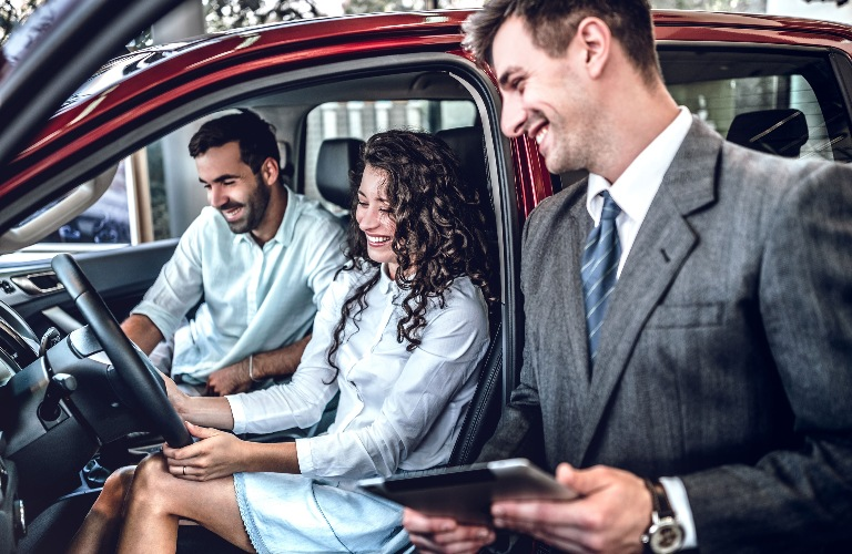 Salesman looking at new vehicle with couple