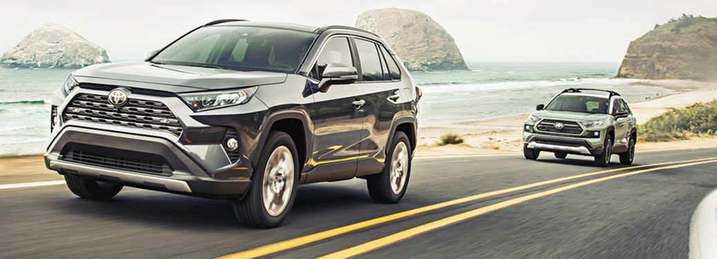 2020 Toyota RAV4 crossovers going down the road next to a lake