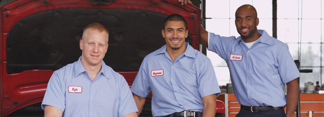 Three mechanics standing in front of a vehicle with the hood open