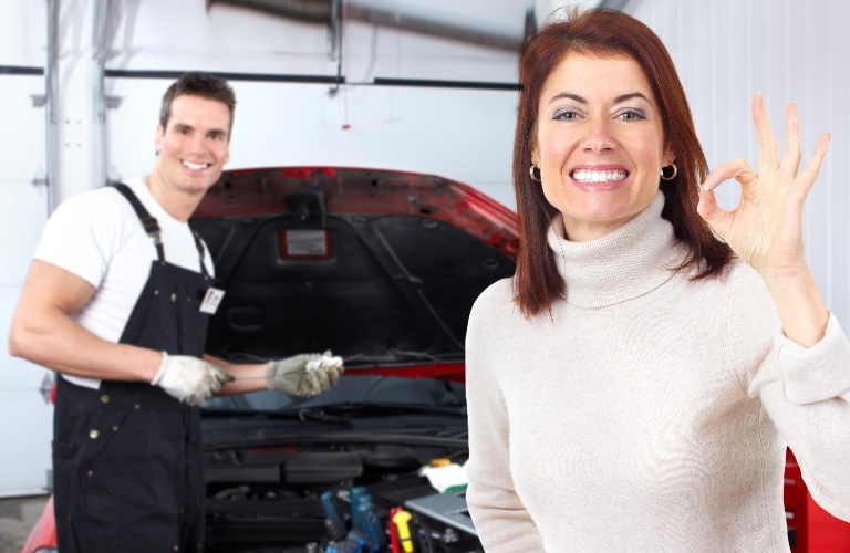 Happy woman and mechanic with hood of vehicle open