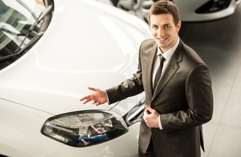 Salesman standing in front of a vehicle in the showroom