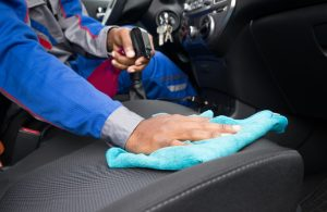 Person cleaning the passenger seat inside a car