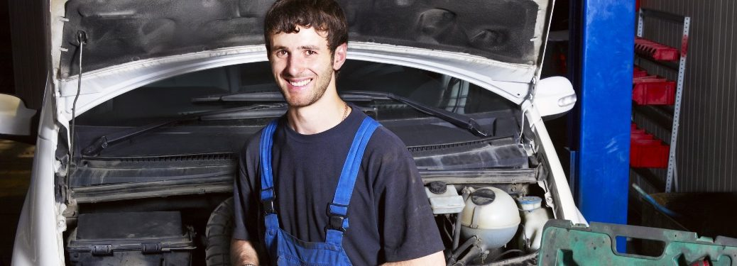 Mechanic standing in front of a vehicle with the hood open