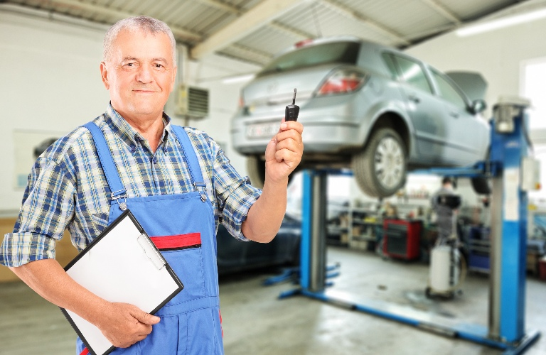 Mechanic holding a key and a vehicle up on a lift
