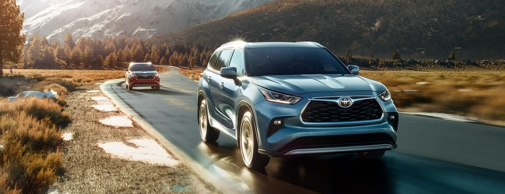 Two 2020 Toyota Highlander SUVs going down the road