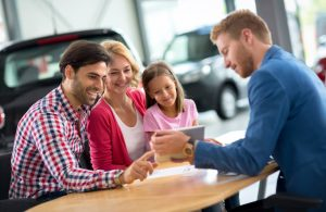 family at desk, looking at ipad with salesman