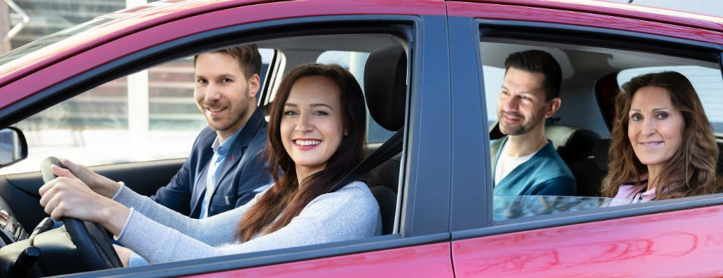 Group of individuals smiling in vehicle