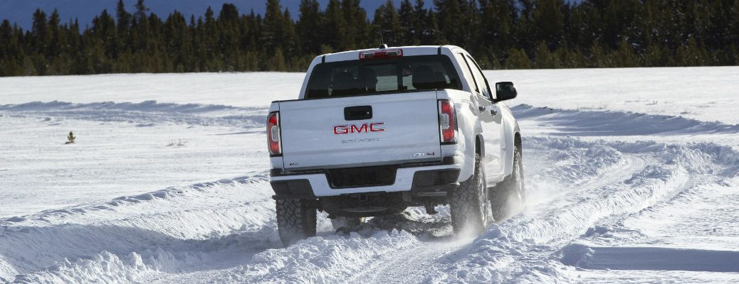 Rear view of white 2021 GMC Canyon AT4 driving through snow